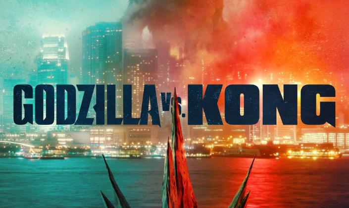 Imagem de capa: a silhueta de King Kong ao fundo, muito grande para ser vista completamente, uma cidade com eletrecidade, mas visivelmente em ruínas e em chamas próxima do mar e os espinhos das costas de Godzilla cortando a imagem e no centro a logo em azul-escuro que diz Godzilla vs. Kong.