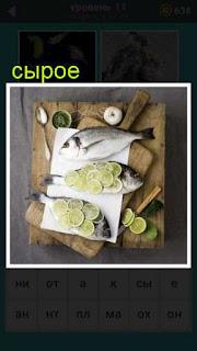 на доске лежит сырая рыба и сверху зеленый лимон кружочками