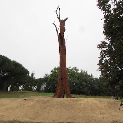 Obra de arte Pequi Vinagreiro, um tronco alto entre árvores
