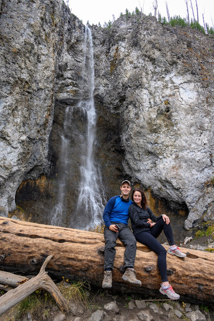 Adventurous Tastes | Man and woman in front of Fairy Falls waterfall in Yellowstone