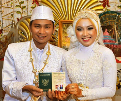 sepasang mempelai memegang buku nikah