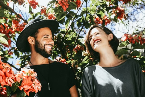 A couple under a flowering tree laughing together