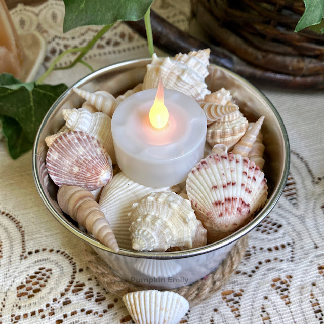 Seashells and a LED candle in a tin vase.
