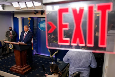 Donald Trump at podium with Exit sign in foreground.