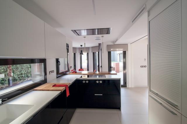 Una cocina en blanco y negro con pen nsula y office for Modelos de techos para galerias