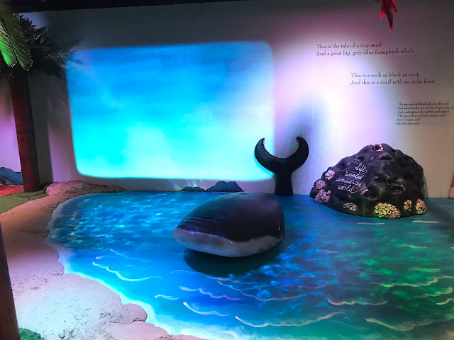 A whale model in a painted sea next to a rock with some writing on