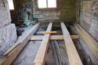Ett foto inifrån ett 200 år gammalt hus. Alla plankor är gamla men på en del är golvet borta och där ligger stora och nya balkar. Under balkarna är det ett ungefär en och en halv meter djupt hål. Mellan balkarna är det lite mindre än en meter. Det ligger verktyg lite överallt och allt är täckt av byggdamm.