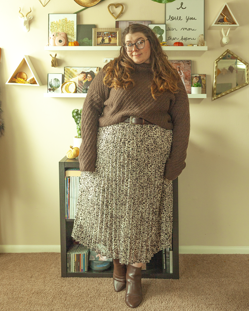 An outfit consisting of a dark brown turtleneck sweater half tucked into a pleated animal print midi skirt and brown ankle boots.