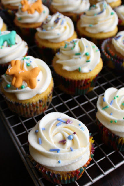 cupcakes decorated with swirls of Russian buttercream, sprinkles and icing decorations