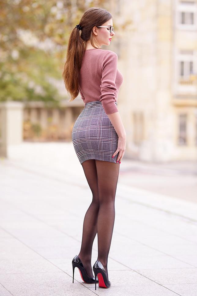 Różowy sweterek, spódniczka w kratkę, czarne rajstopy i trencz