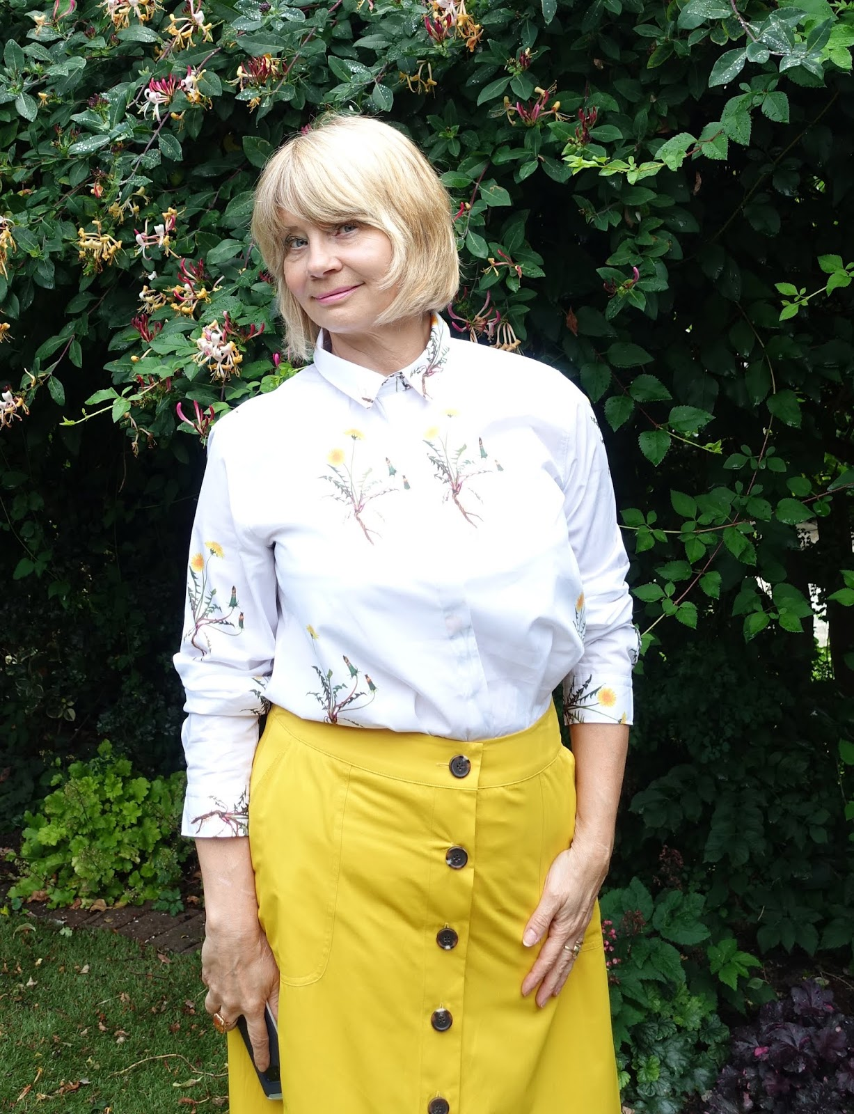 Honeysuckle backdrop for over-50s woman in golden yellow skirt and white blouse with yellow flower print