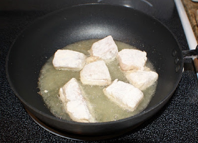 this is a pan of seasoned floured bite sized pieces of haddock fried in oil in a grey pan