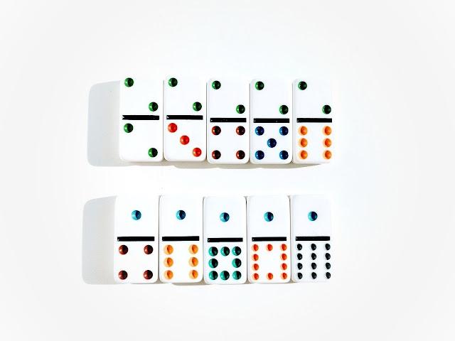 na zdjęciu dziesięć kamieni domino ustawione w dwa rzędy z oczkami skierowanymi do góry