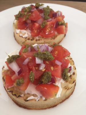2 crumpets topped with cream cheese, tomato, red onion and pesto