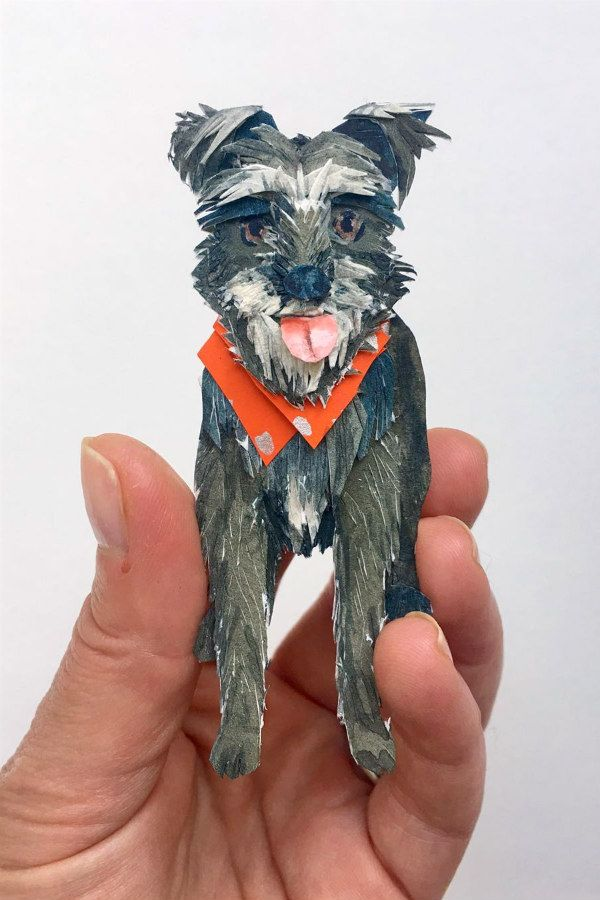 papercut of black and gray rescue dog wearing orange neckerchief in hand of artist