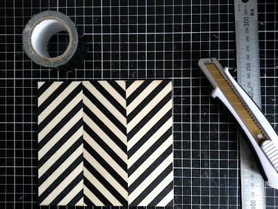 Three rectangular pieces of plywood, printed with black stripes, laid out on a cutting mat along with a roll of black duct tape, a metal ruler and a utility knife.
