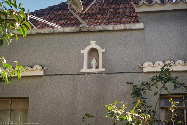 Detalhe de capelinha com imagem de Nossa Senhora na fachada de uma casa