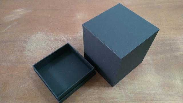 Caixa aberta revestida com papel preto.