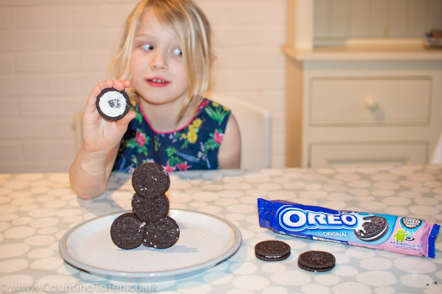 A girl pulling a silly face while building a tower of Oreo cookies and an oreo promotional great cookie quest wrapper in the foreground