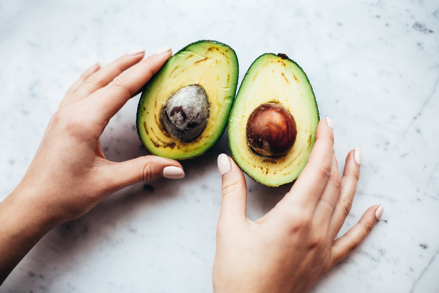 two female hands are showing a cut avocado