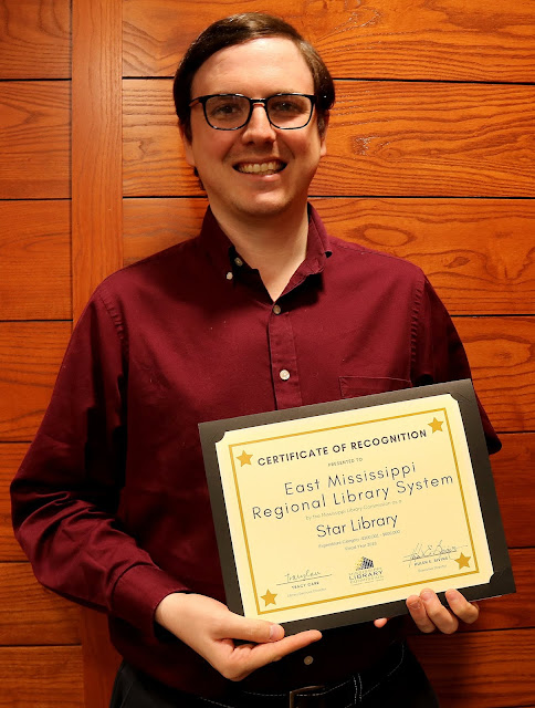 smiling man holds a certificate of recognition for east mississippi regional library system