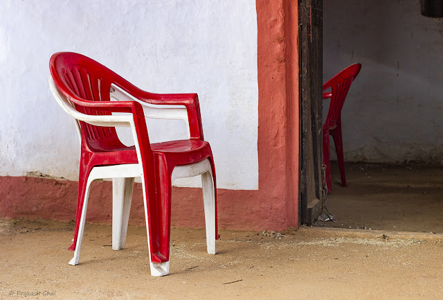 A Minimalist Photograph of Idle Plastic Chairs contrasting each other, one being Inside and the other being outside.