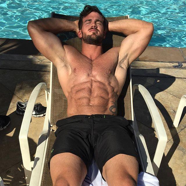 handsome-hairy-fit-body-man-beard-sun-tanning-shirtless-pool