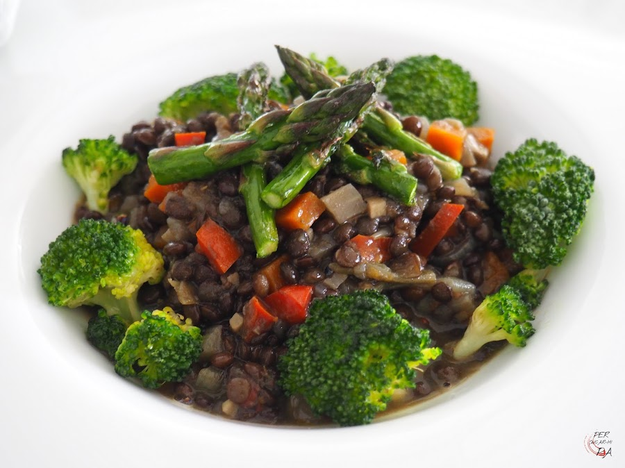 Guiso vegetariano de lentejas caviar, o lentejas beluga, con verduras y ras el hanout, con brócoli y puntas de espárragos trigueros.