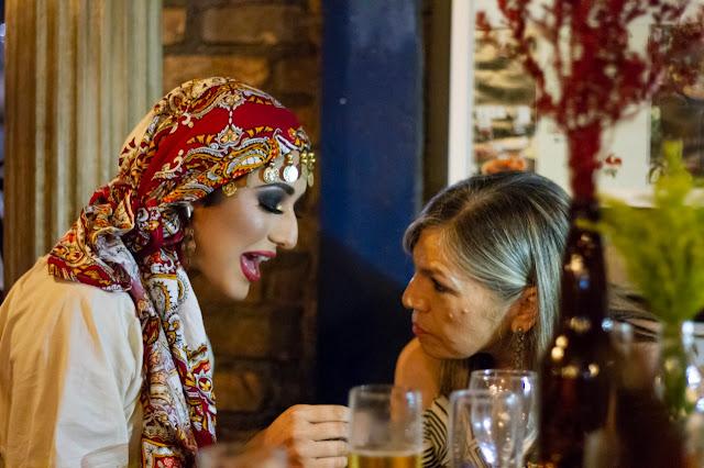 Interação da personagem cigana com convidados de casamento durante o jantar.