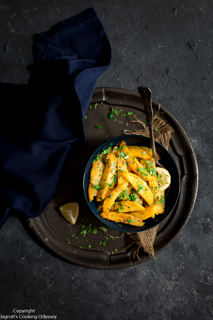 yellow Potato curry served in a blue bowl with stainless steel spoon.