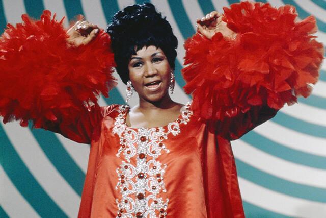 cantora aretha franklin usando um vestido vermelho com plumas nas mangas