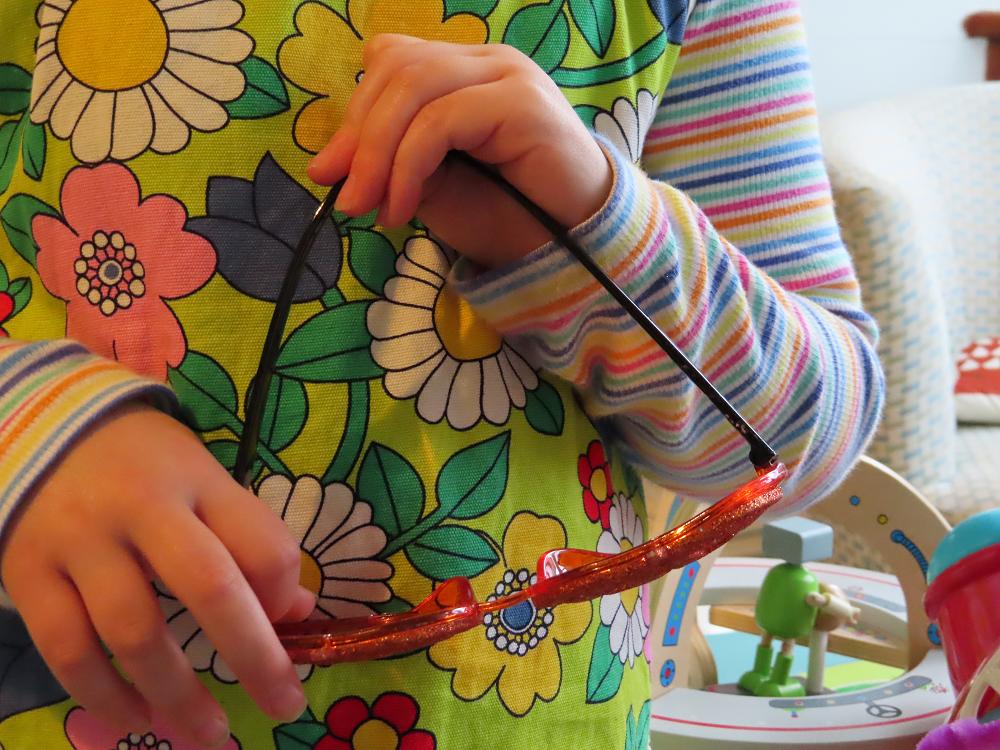 Child hands holding novelty pumpkin sunglasses