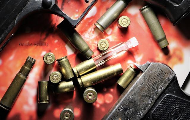 Próbka perfum zakończona łuską naboju 9mm w otoczeniu łusek różnych kalibrów i broni ASG