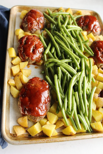 raw green beans piled on top of sheet pan with partially cooked potatoes and mini meatloaves