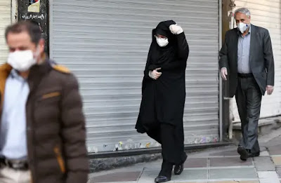Iranian people wear protective masks to prevent contracting a coronavirus, in Tehran, Iran February 29, 2020 (photo credit: REUTERS)