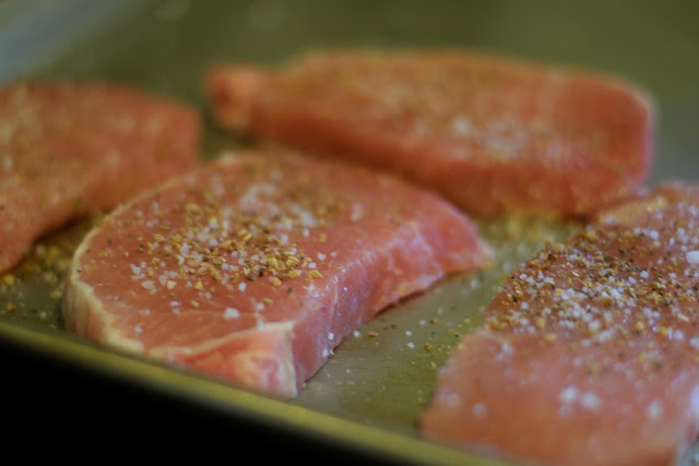 The pork chops being seasoned with salt and lemon pepper seasoning.