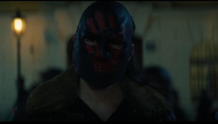 Imagem: um dos Apátridas, uma pessoa branca com um casaco marrom e uma máscara preta que esconde o seu rosto, com furinhos no lugar da boca e uma marca de uma mão vermelha sobre os olhos.