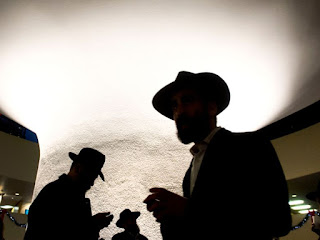 Orthodox Jews are silhouetted against the rotunda in City Hall during the Chanukah event called 'Occupy City Hall' in Toronto on Sunday, December 9, 2012.Darren Calabrese/National Post