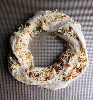 wreath of braided bread dough stuffed with cheddar and bacon, ready to rise
