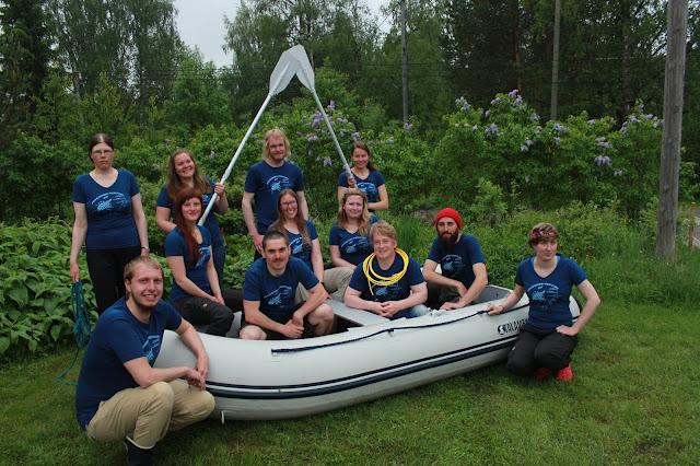 12 henkeä poseeraa nurmikolla kumiveneen ympärillä meritiimipaidat päällä