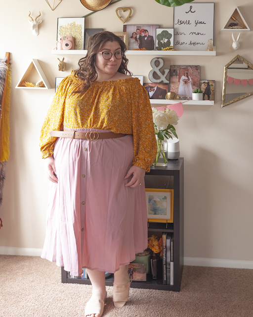 An outfit consisting of a yellow long sleeve microfloral print off the shoulder blouse tucked into a muted pink button down midi skirt and pink slide sandals.