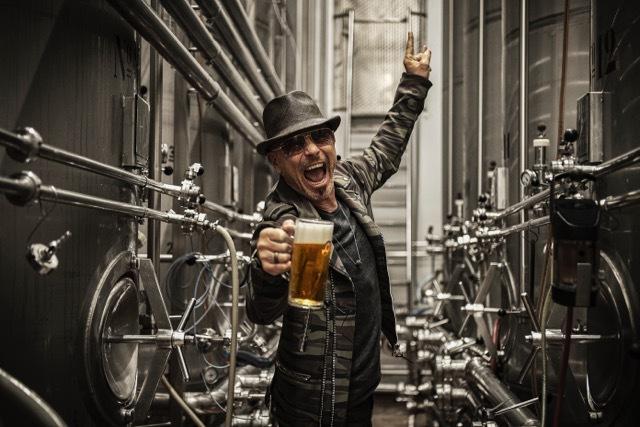 Rudolf Schenker dentro de uma fabrica de cerveja segurando um caneco de cerveja com uma mão, fazendo pose de grito e o simbolo rock and roll com a outra mão.