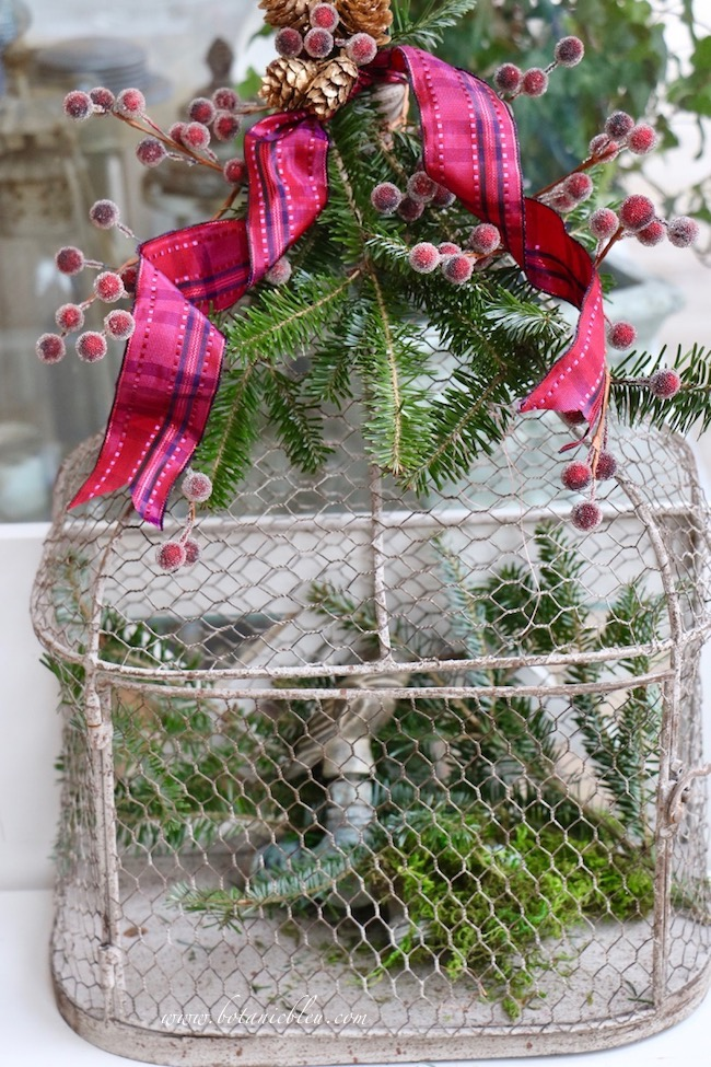 Christmas red plaid berry birdcage uses a mix of faux berry stems, fresh tree clippings, preserved moss, and tiny pine cones