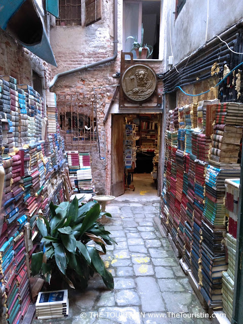Courtyard with books stacked along the brick walls and open entrance door to a bookshop.