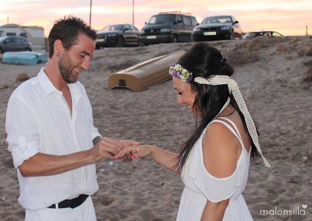 El novio poniendo el anillo de boda a la novia en una boda ibicenca vestidos de blanco, tocado TARIFA Malonsilla