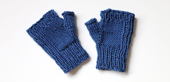 A pair of hand knit blue fingerless on a white background.