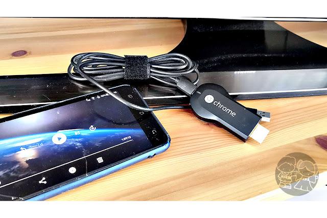 El dongle Chromecast, y un móvil listo para castear o proyectar una película en la tela a través del dispositivo.