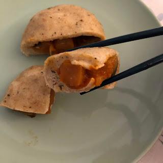Morceau de Banh bao végétariens à la ratatouille entre deux baguettes chinoises (brioches vapeur vietnamiennes)