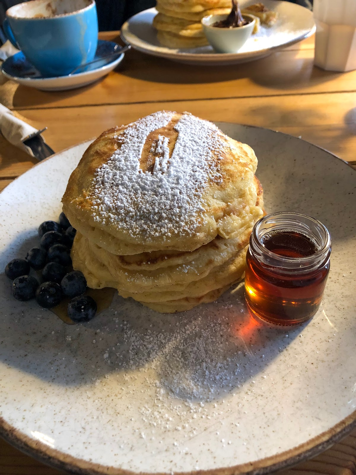 A stack of fluffy American style pancakes served with a blueberries, a jar of syrup and a dust of sugar
