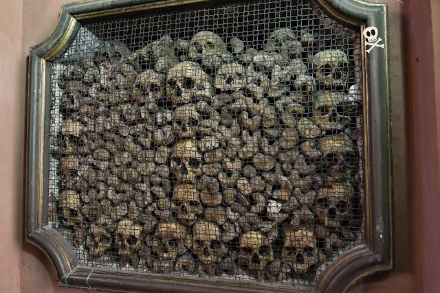 Marco abierto en la pared lleno de calaveras y huesos largos en composición casi artística.